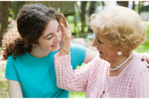 Beautiful teen girl and her loving grandmother smiling at eachother.
