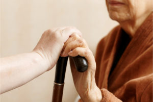 Carer-and-older-person-hands-and-cane-resized