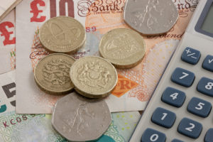 British coins and notes with a calculator