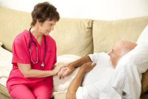 Compassionate home health nurse holds an elderly patient's hand.