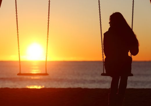 Single woman alone swinging on the beach and looking the other seat missing a boyfriend
