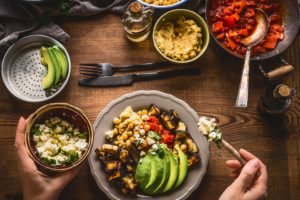 Female woman hands served healthy vegetarian meal in bowl with chick peas puree, roasted vegetables , red paprika tomatoes stew, avocado and seeds . Clean eating, dieting, vegetarian food concept