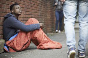 Homeless Teenage Boy In Sleeping Bag On The Street