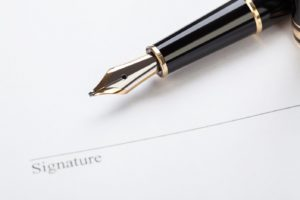 macro closeup sign document contract pen filler white background blank