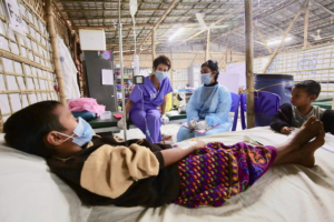 A UK Emergency Medical Team paediatric nurse monitors a young girl being treated for diphtheria in the Kutupalong refugee camp, Bangladesh. Diphtheria is a highly contagious and potentially fatal bacterial infection.    Photo credit: Russell Watkins/DFID, licensed through Flickr.