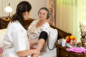 Female doctor checking blood pressure to senior woman at home. Elderly healthcare concept.