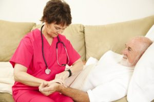 Home health nurse taking the pulse of an elderly patient.