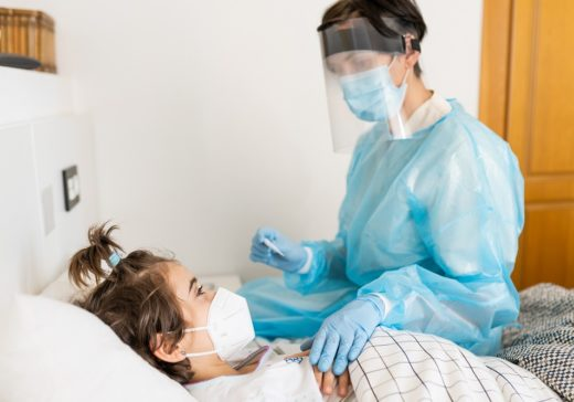 Doctor protected by personal protective equipment examining a little girl with a stethoscope at home.