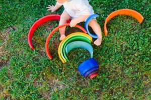 Baby playing with a colorful wooden rainbow on the grass, children's intellectual and mental development.