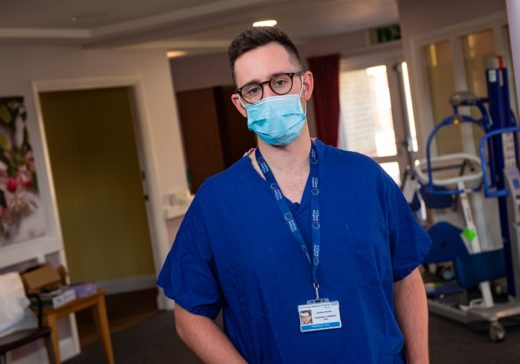 Photo 1 Dr Jonathan Riordan in his scrubs on the Inpatient Unit at St Clare Hospice_