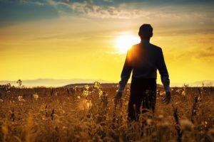 Calm manager walking towards the sunrise