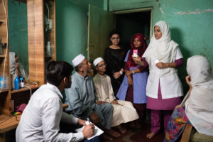 Senior Staff Nurse Arifa Anjum briefs patient Soubia Akter's  family on medicine feeding procedure in the presence of PCA Mousomi Akter and volunteer Khusbu while Field Coordinator Md. Saiful Hoque takes notes.