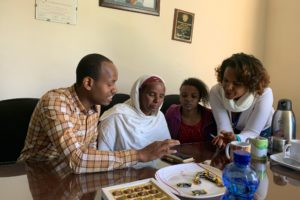 Ato Ephrem Abathun and nurse Yohanna showing patients how to use the app at Hospice Ethiopia.