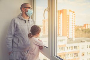 Little girl and her father in medical mask looking through the window. Isolation at home for self quarantine. Concept home quarantine, prevention COVID-19. Coronavirus outbreak situation